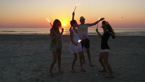 Group of friends celebrating with sparklers at the beach at sunrise stock footage