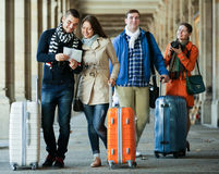 Group of friends checking direction. Group of friends with luggage checking a direction in a map outdoor Royalty Free Stock Images
