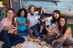 Group of friends cheering with beer bottles. In cafeteria Stock Photo