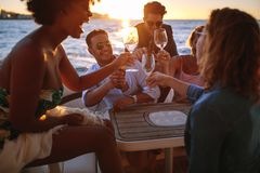 Group of friends cheering with drinks at boat party. Group of happy friends cheering with wine and beers at boat party. Diverse men and women having drinks at stock photography