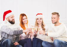 Group of friends in Christmas hats celebrating Stock Photo