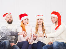 Group of friends in Christmas hats celebrating Royalty Free Stock Images