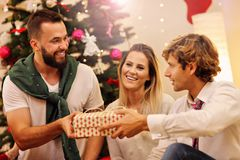 Group of friends with Christmas presents at home Stock Photos