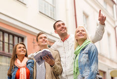 Group of friends with city guide exploring town Royalty Free Stock Photo