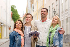 Group of friends with city guide exploring town Stock Image