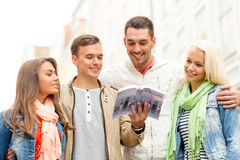 Group of friends with city guide exploring town. Travel, vacation and friendship concept - group of smiling friends with city guide exploring town Stock Photos