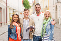 Group of friends with city guide exploring town Royalty Free Stock Image