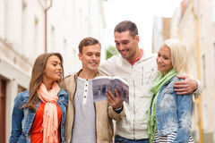 Group of friends with city guide exploring town Stock Photos