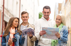 Group of friends with city guide, map and camera Royalty Free Stock Photos