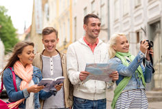 Group of friends with city guide, map and camera Royalty Free Stock Image