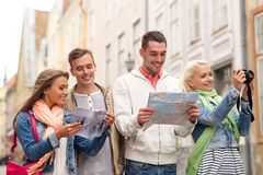 Group of friends with city guide, map and camera Royalty Free Stock Images