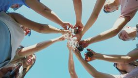 Group of friends clink wine glasses and beer bottles. A group of friends clink wine glasses and beer bottles against the blue sky on a sunny summer day, the stock video