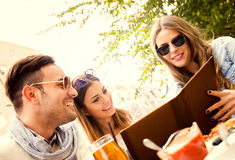 Group Of Friends. Close-up of three young cheerful people drinking beer outdoors. They are laughing and having a great time Stock Photos