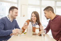 Group of friends. Close-up of three young cheerful people.Friends smiling and sitting in a cafe, drinking coffee and enjoying together Stock Photos