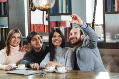 Group of friends with coffee and looking at smartphone Stock Photography