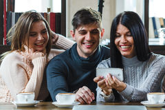 Group of friends with coffee and looking at smartphone Stock Image