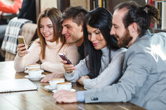Group of friends with coffee and looking at smartphone Stock Photos
