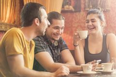 Group of three friends in a coffee shop. Group of friends in a coffee shop, discussing some content on their phone Royalty Free Stock Photos