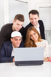 Group of friends and colleagues looking at laptop together. Beautiful group of friends and colleagues looking at laptop together smiling Stock Photos
