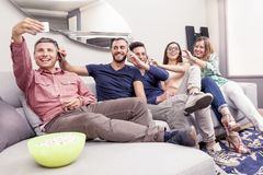 Group of friends on couch takes a selfie in a funny way. Group of friends sitting on the couch to the phone at the same time  in a modern apartment Stock Photography