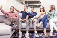Group of friends on couch takes a selfie in a funny way. Group of friends sitting on the couch to the phone at the same time  in a modern apartment Stock Photos