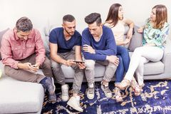 Group of friends on the couch talking and looks at the phone. In a modern apartment Stock Photo
