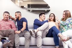 Group of friends on the couch to the phone at the same time. Group of friends sitting on the couch to the phone at the same time  in a modern apartment Stock Photos