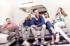 Group of friends on the couch to the phone at the same time. Group of friends sitting on the couch to the phone at the same time in a modern apartment Royalty Free Stock Photo