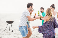 Group of friends dancing on the beach with beer bottles Royalty Free Stock Photo