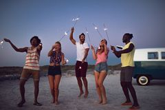 Group of friends dancing with sparklers on the beach at dusk. Front view of happy group of diverse friends dancing with sparklers on the beach at dusk royalty free stock photography