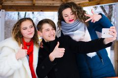 A group of friends do selfie in the winter in a clearing royalty free stock photo
