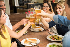 Group of friends drinking beer. Closeup of a group of young adults drinking beer and making a toast in a restaurant Stock Image