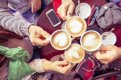 Group of friends drinking cappuccino at coffee bar restaurant. People hands cheering and toasting with upper view point - Social gathering concept with men stock photography