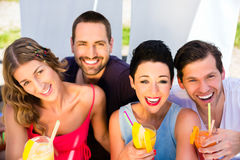 Group of friends drinking cocktails in beach bar Royalty Free Stock Images