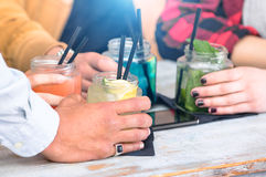 Group of friends drinking cocktails at fashion bar restaurants. Side view point of people hands with smartphone - Social gathering concept with addicted men Royalty Free Stock Photos