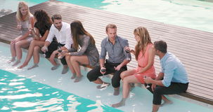 Group of friends drinking with foot in swimming pool
