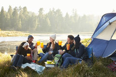 Group of friends drinking outside their tent near a lake Royalty Free Stock Image