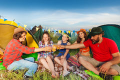 Group of friends drinking outside their tents Royalty Free Stock Images