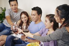 Group of friends drinking wine. Group of cheerful friends sitting on sofa and toasting with wine glasses stock photos
