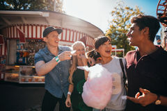 Group of friends eating candyfloss at fairground. Group of friends having fun while eating cotton candy at fairground. Young men and women with candyfloss at Royalty Free Stock Photos