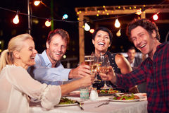 Group of friends eating dinner at rooftop restaurant Stock Image