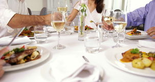 Group of friends eating dinner together and toasting with wine stock footage