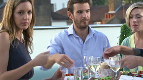 Group Of Friends Eating Meal On Rooftop Terrace. Group of friends enjoying evening meal on rooftop terrace.Shot on Sony FS700 in PAL format at a frame rate of stock video footage