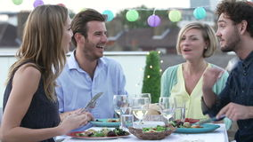 Group Of Friends Eating Meal On Rooftop Terrace Royalty Free Stock Photos