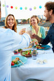 Group Of Friends Eating Meal On Rooftop Terrace Royalty Free Stock Images