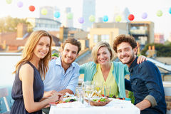 Group Of Friends Eating Meal On Rooftop Terrace. Sitting Down Smiling At Camera Stock Photos
