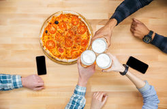 Group of friends eating pizza and drinking beer Royalty Free Stock Photography