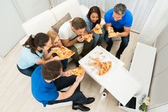 Group of friends eating pizza Stock Images