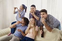 A group of friends eating pizza while sitting on the couch. A group of friends eating pizza while sitting on the couch in the room Stock Photo
