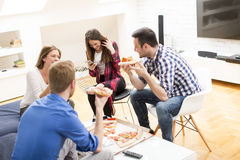 Group of friends eating pizza together at home Royalty Free Stock Photos